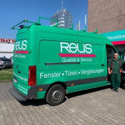 Mann-steht-in-der-Autotuer-eines-gruenen-Transporters-mit-Firmenwerbung-von-Reus-Hanau