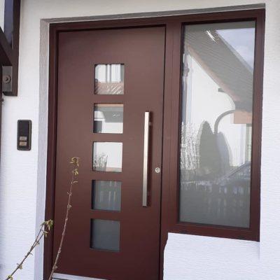 Hauswand-mit-moderner-Haustuer-dunkel-rot-braun-mit-quadratischen-Fensterelementen