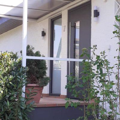 Eingangsbereich-aussen-mit-grauer-Haustuer-und-Fensterelement-aus-Anthrazit