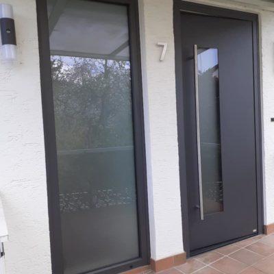 Graue-Haustuer-aus-Anthrazit-mit-grossem-Fensterelement-nebendran