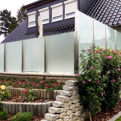 Wohnhaus-mit-Garten-der-rundum-geschuetzt-ist-dank-eines-Glas-Sichtschutzes