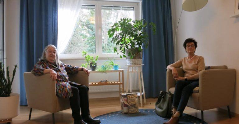 zwei-Frauen-sitzen-sich-gegenueber-jeweils-in-einem-Sessel-Ort-ist-ein-wohnliches-Zimmer
