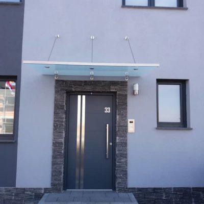 dunkelgraue-Haustuer-mit-Glasdach-an-einer-hellgrauen-Hauswand