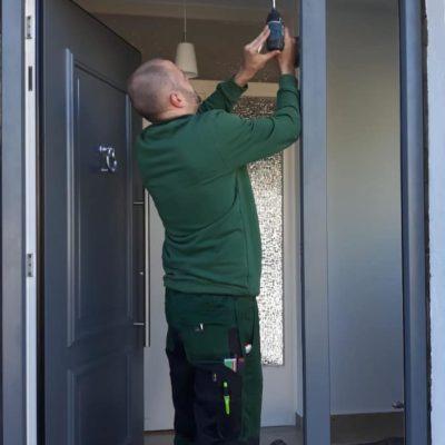 Reus-Hanau-Mitarbeiter-in-gruener-Arbeitskleidung-montiert-graue-Haustuer