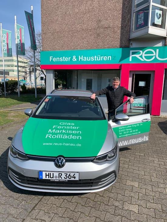 Mann-steht-in-der-Autotuer-eines-gruenen-Volkswagen-Autos-mit-Firmenwerbung-von-Reus-Hanau-darauf