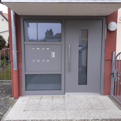 graue-Haustuer-mit-Fensterelementen-fuer-Wohnungskomplex-mit-mehreren-Klingeln-und-Briefkaesten